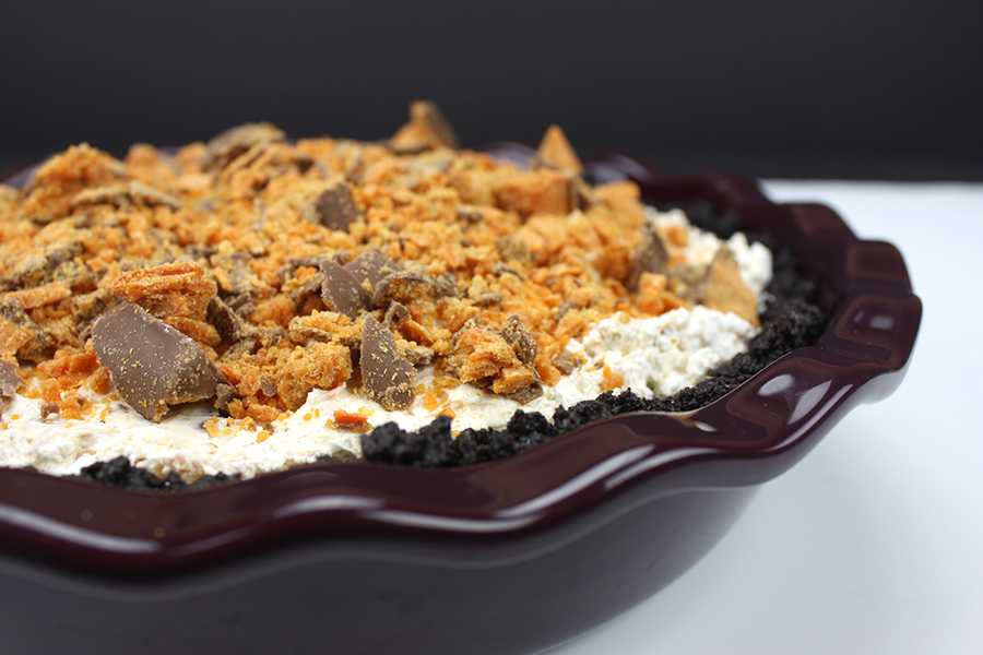 no bake Butterfinger pie garnished with crushed butterfingers in purple pie plate