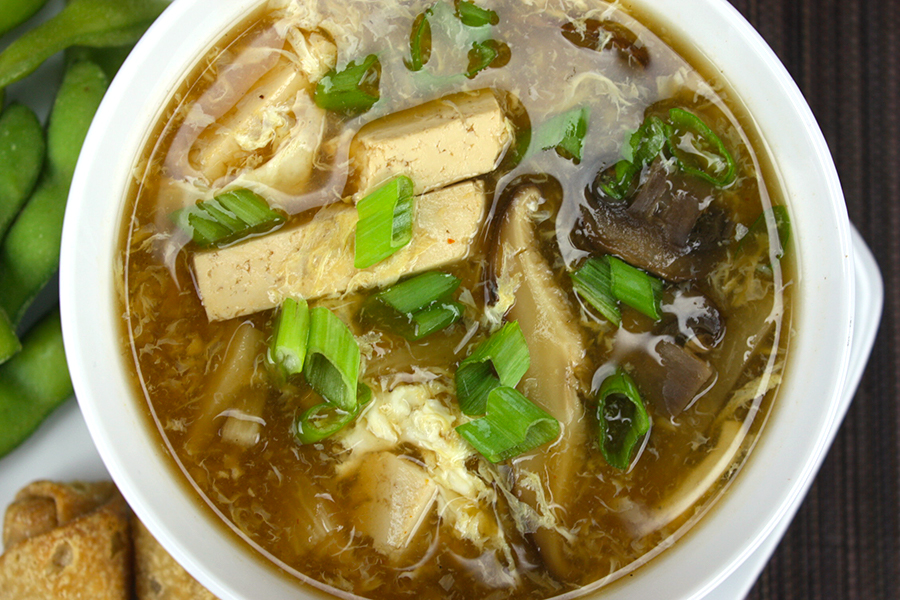 close up of hot and sour soup garnished with chopped green onions