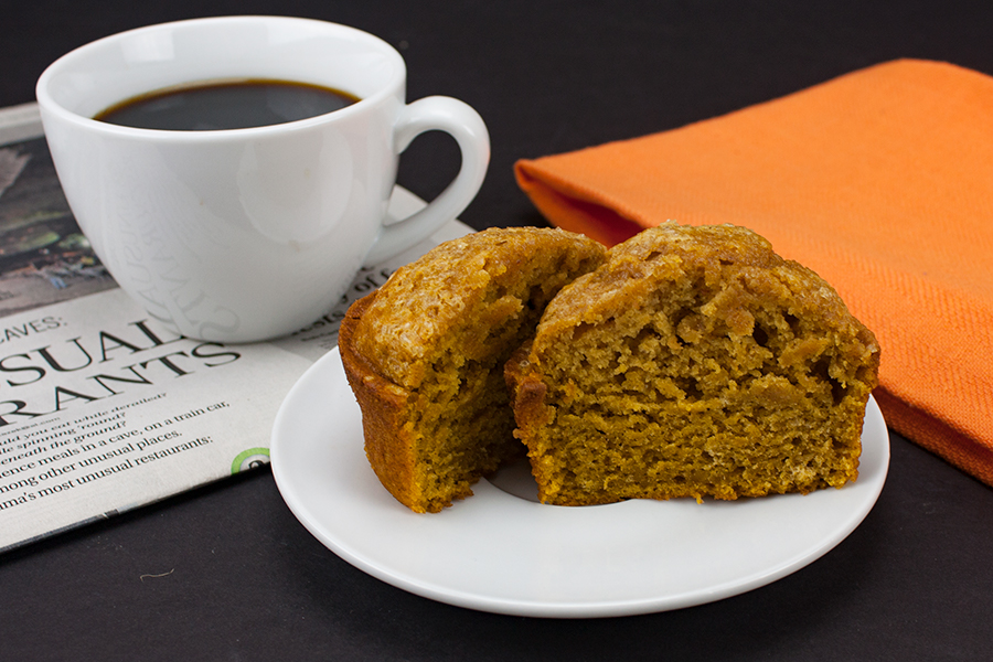 Pumpkin Muffin slice in half on a white plate with a cup of coffee in a white mug on a newspaper