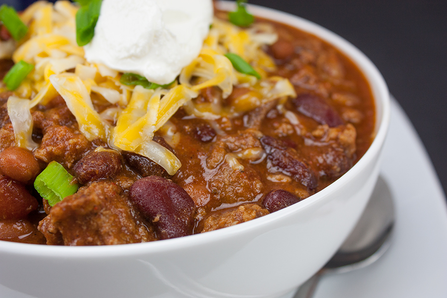 chili in white bowl topped with cheese green onions sour cream