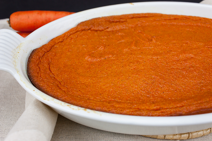 baked carrot souffle in a white oval casserole dish