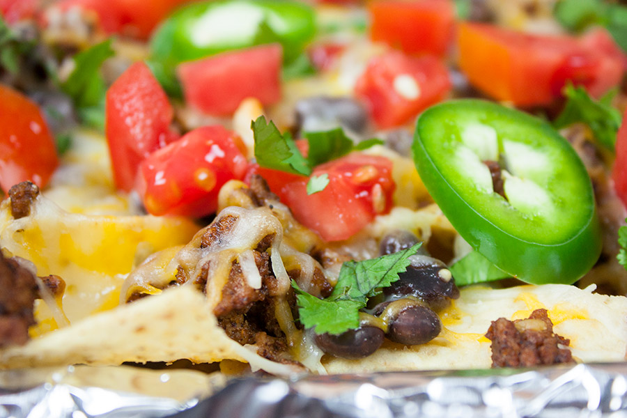 close up of baked nachos ground beef fresh diced tomatoes fresh sliced jalapenos
