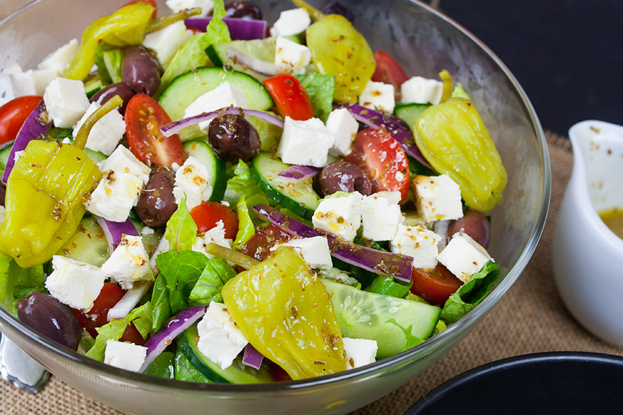 Greek Salad mixed with dressing in a clear glass serving bowl