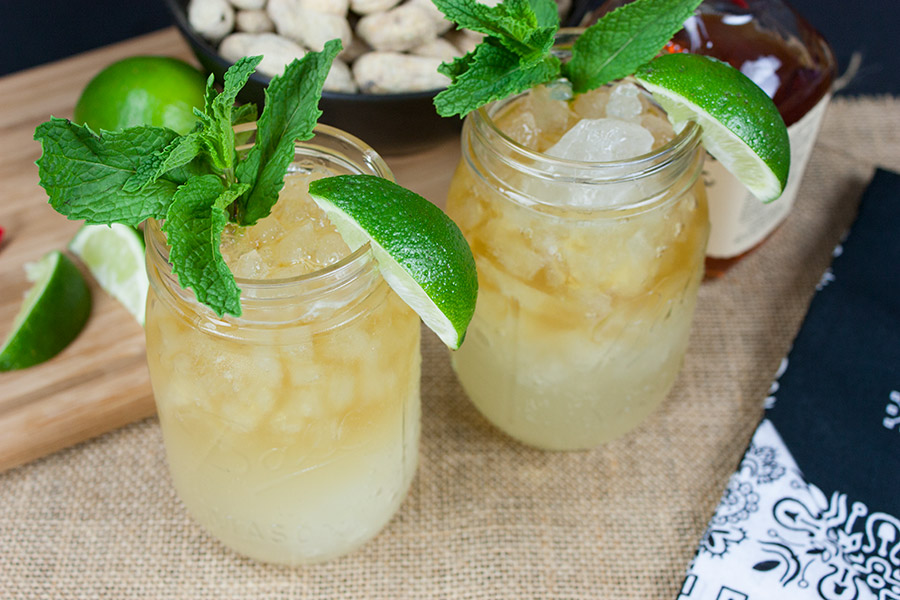 close up of two Kentucky Mule drinks in mason jars garnished with mint and lime wedges