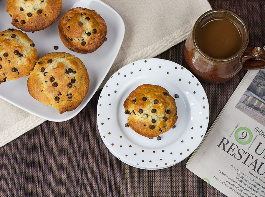 Chocolate Chip Muffin on white plate single one on white plate with gold dots newspaper coffee mug