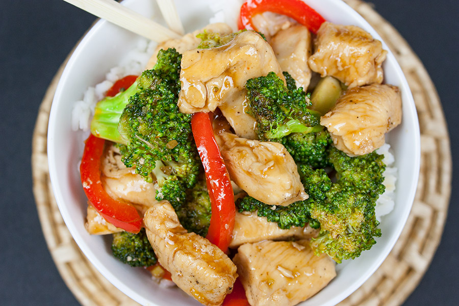 chicken broccoli stir fry in a white bowl over rice with chopsticks