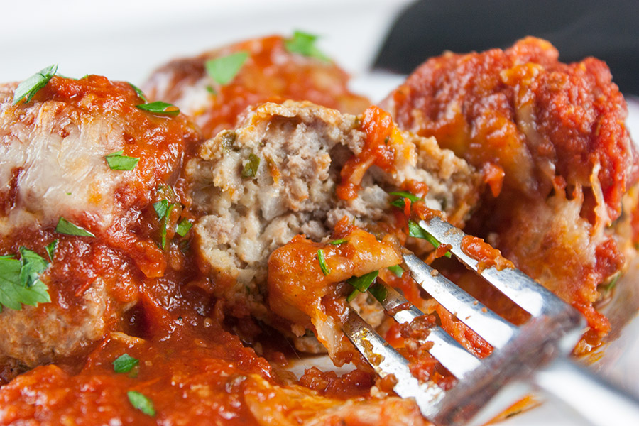 close up of Baked Parmesan Meatballs one cut open on a fork