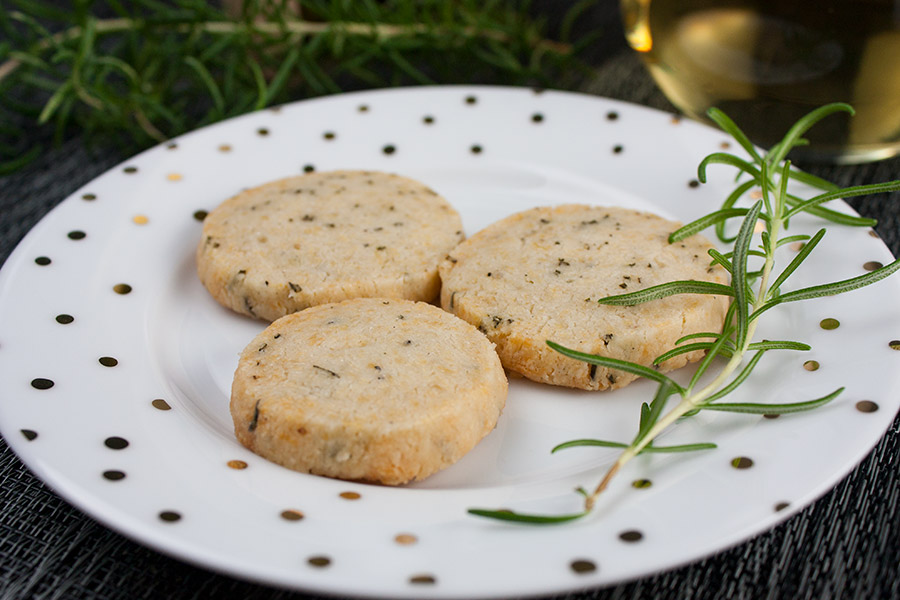three Parmesan rosemary shortbread crackers on white plate gold dots fresh rosemary sprig