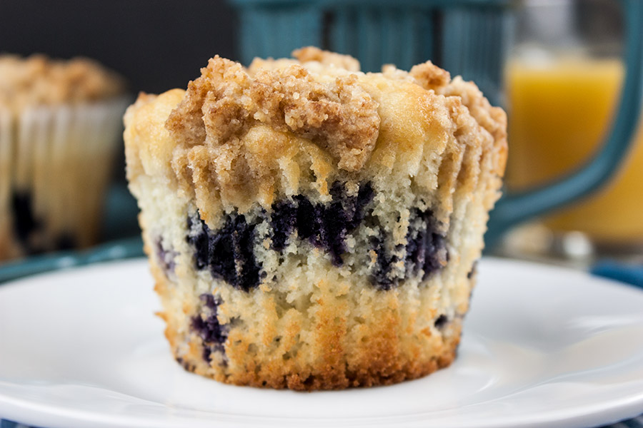 lemon streusel blueberry muffin close up on white plate