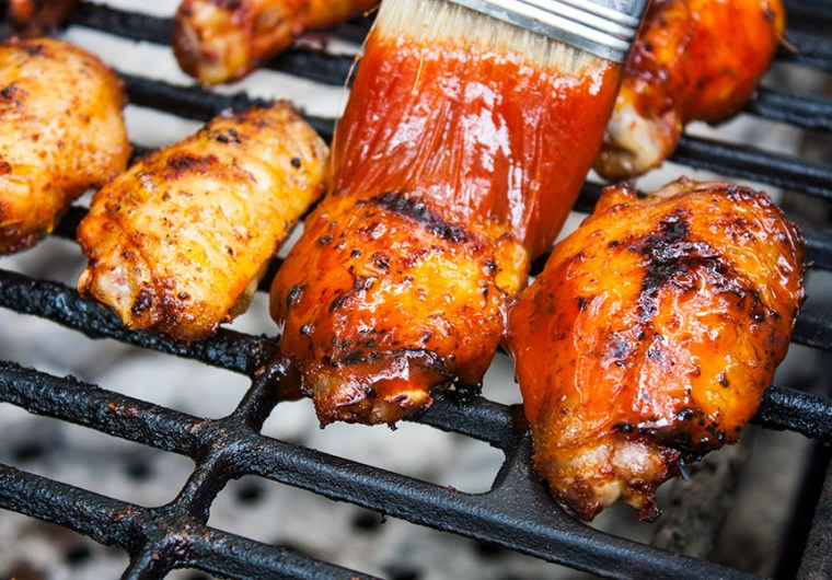 wings on the grill grate brushing with sauce