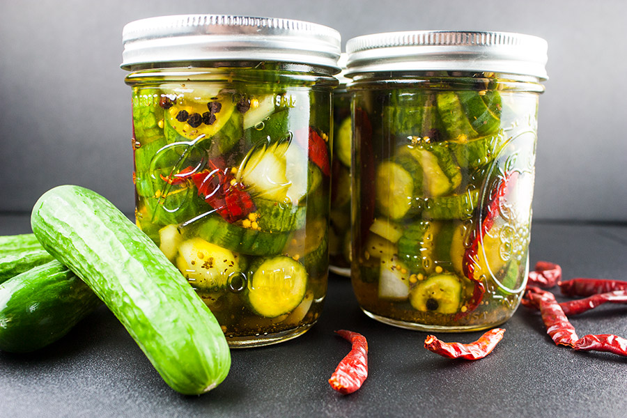 Spicy Bread and Butter Pickles in canning jars fresh pickles and dried peppers scattered around