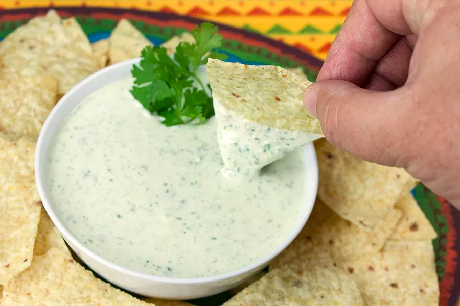 chip dipped in cilantro dip