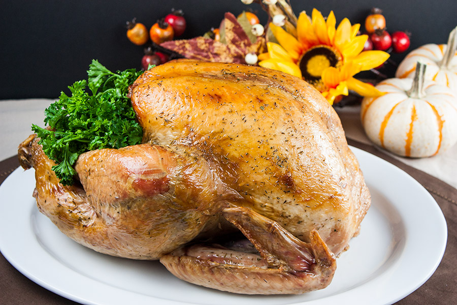 whole roasted golden brown turkey on a white platter garnished with parsley