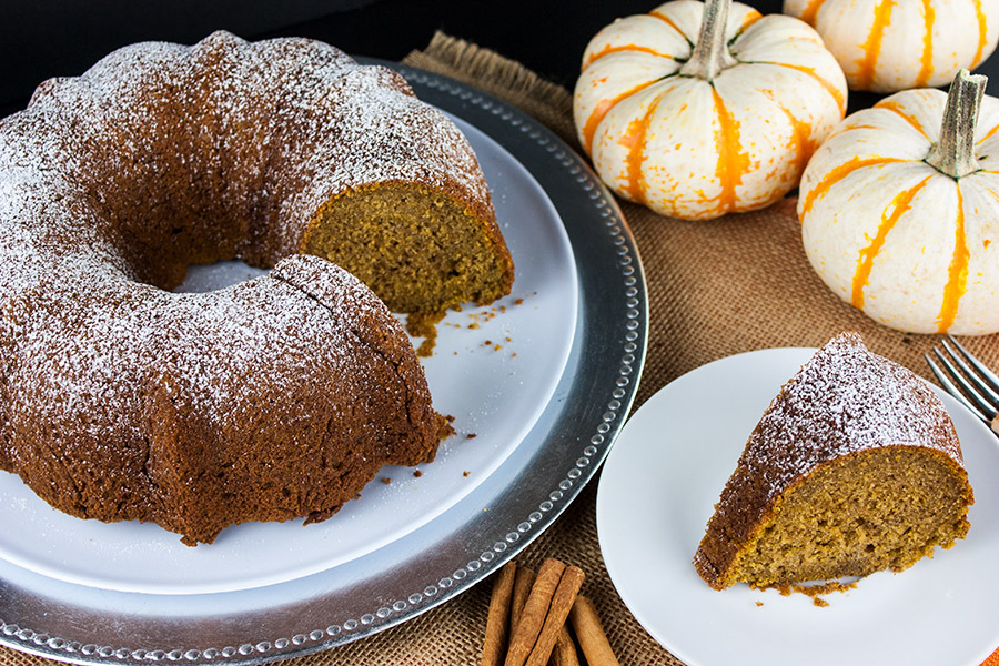 cake on a white cake plate with small white and orange pumpkins