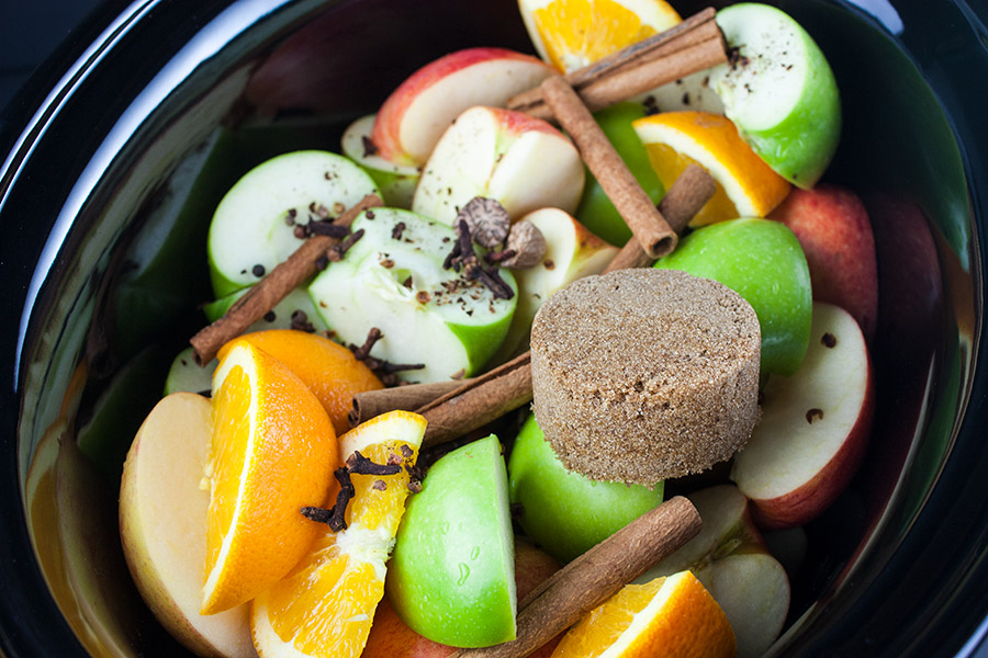 slow cooker filled with sliced apples oranges and spices