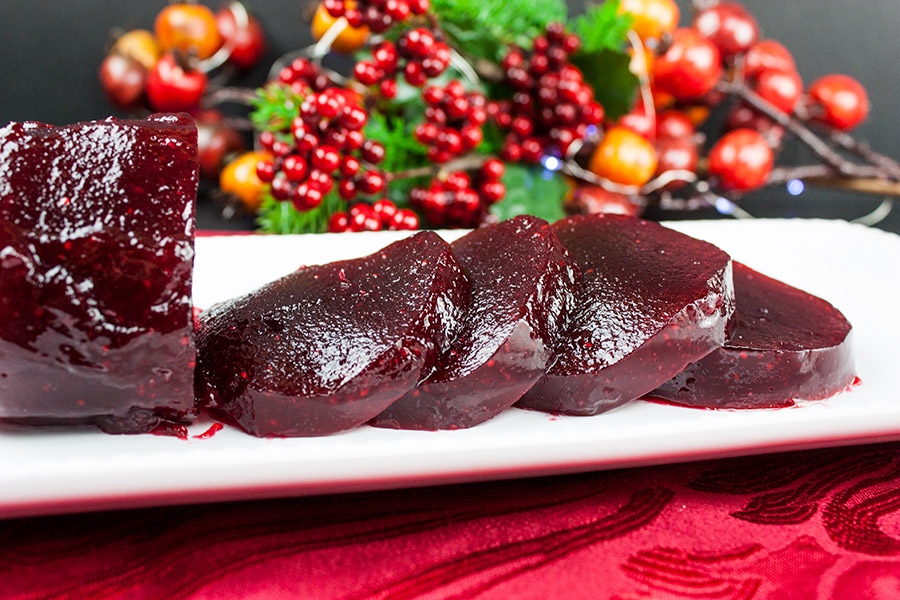 unmolded cranberry sauce shaped like a jar and sliced in serving slices on a white platter
