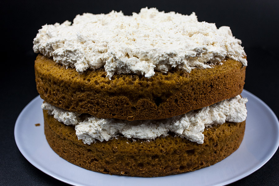 cake layers with cream cheese filling spread in the middle and on top