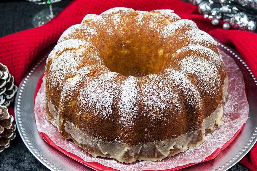 baked eggnog bundt cake on silver and red plate dusted with confectioners' sugar