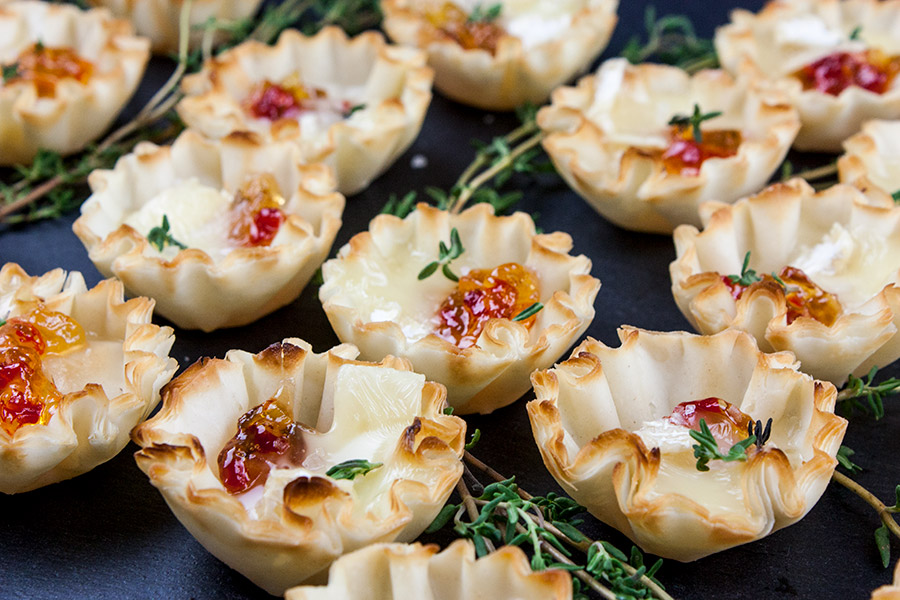 pepper jelly brie bites arranged on slate with fresh thyme sprigs