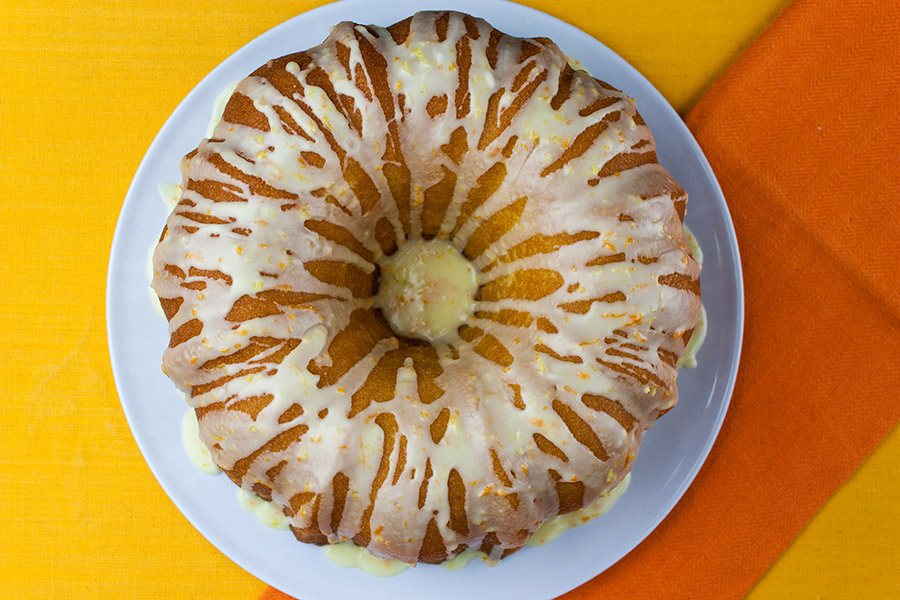 Lemon-Orange Pound Cake drizzled with glaze on white plate with yellow and orange background
