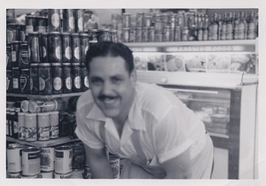 A black and white photo of my dad inside his deli. In this blog I explore the ties between writing, food, and family history.