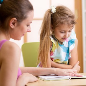 Teacher helping child to read small