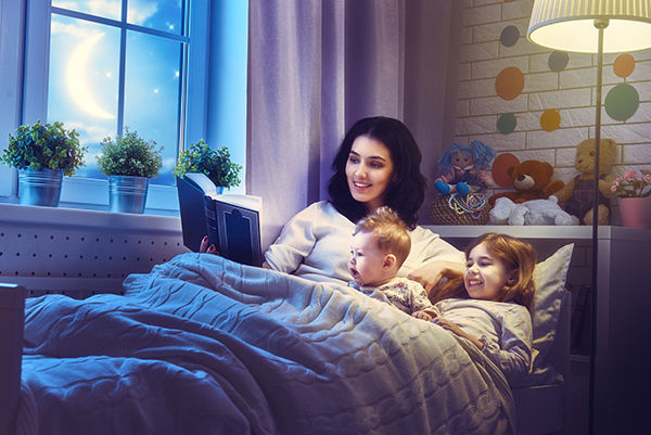 A mother reads to two young children at night before bedtime.