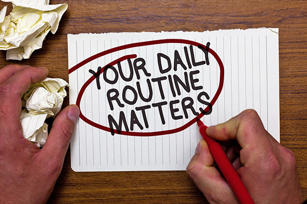 """Man writing on paper and circling with red pen the quote """"Your daily routine matters."""" Blog by children's author Don M. Winn."""