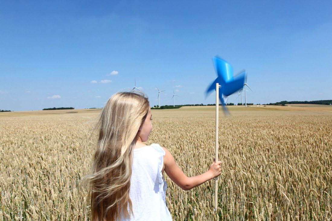 Girl with long blong hair facing away from viewer stands in wheatfield with industrial windmills in the background, holding a spinning blue pinwheel in her hand.