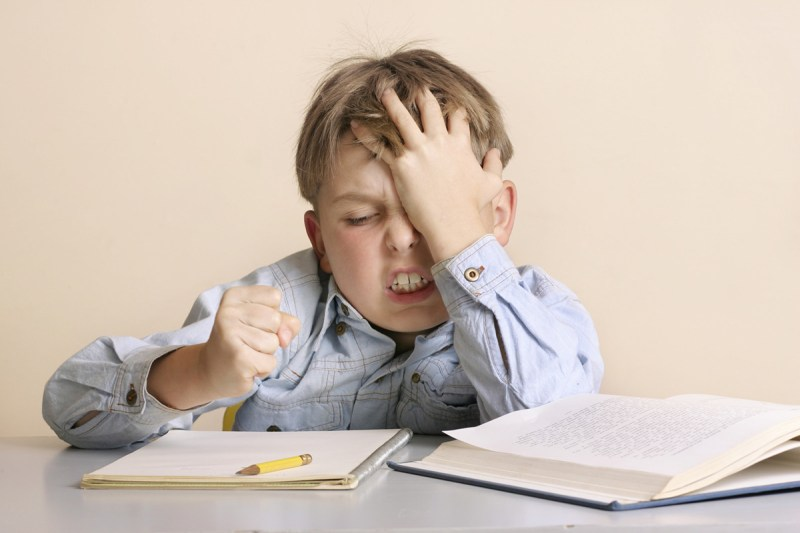 A frustrated boy shakes his fist at a notebook as he sits at a table doing his homework which involves reading and writing.