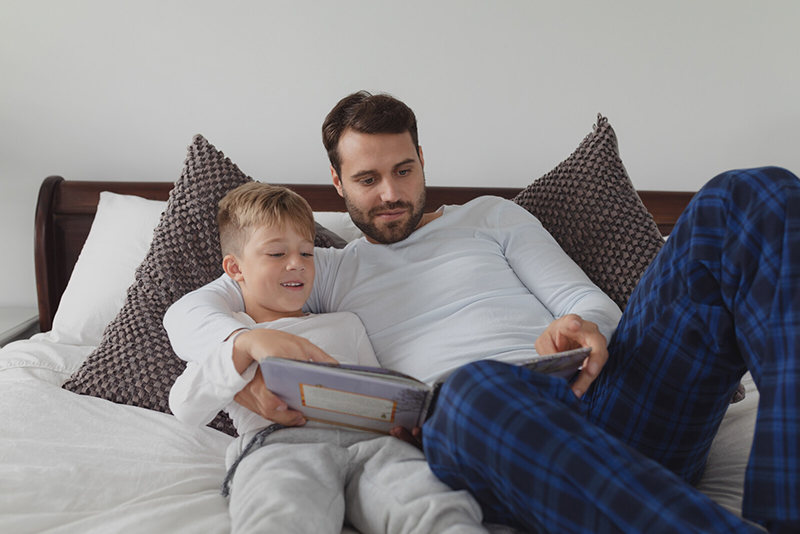 A father and son read together in their pjs. Reading together can help kids avoid COVID academic slide.