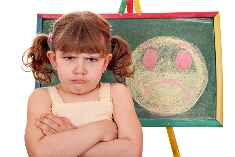An angry little girl with curled red hair in pigtails faces the viewer with her arms crossed. Behind her is a chalkboard with a frowny face drawn upon it. Drawing is a way of helping dyslexic children illustrate their feelings when they are stressed, especially about the uncertainty of new circumstances and learning at home.