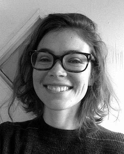 Black and white photo of artist and editor Edith Zimmerman. She wears glasses and has a big smile.