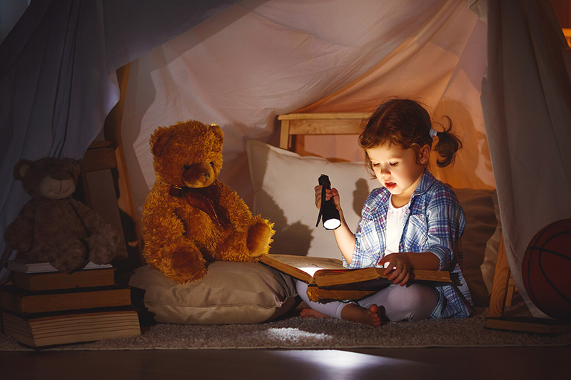 A little girl reads a book with a flashlight in a tent made out of a blanket. A flashlight is just one of many affordable ways to make learning fun.