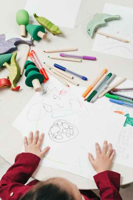 A child sits at a table, making a drawing for his homework while the child's toys sit out of reach. What can parents do if they feel their child has too much homework?