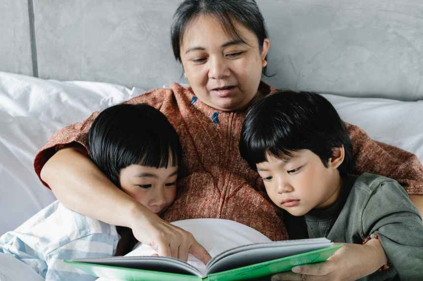 ethnic mother and little kids reading book in bed