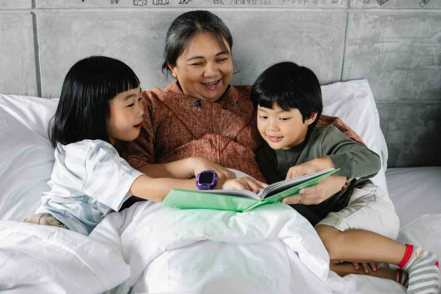A mother reads to her two children as they cuddle for a moment of connection, escape, and imagination, just a few of the benefits of the power of stories during difficult times.