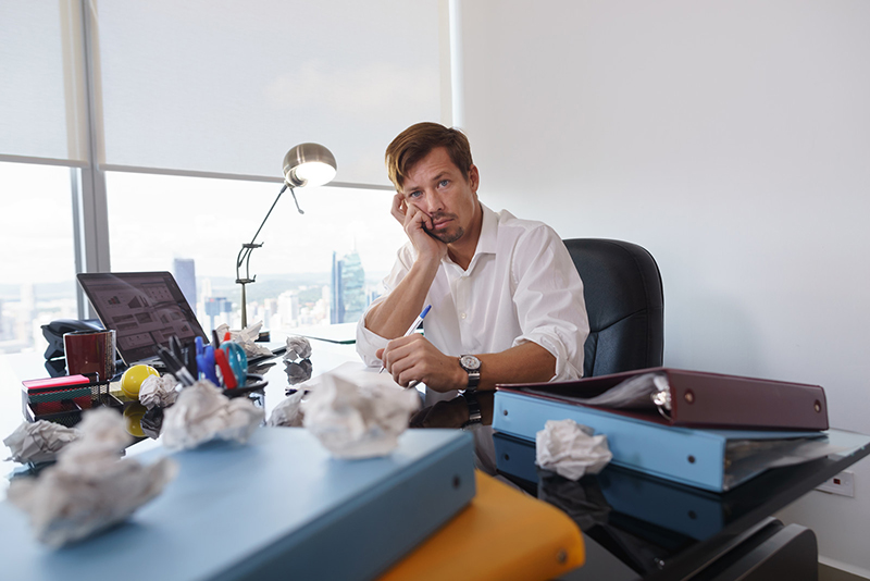 An exhausted looking man sits at his office desk leaning his head on his hand and looking into the camera. He is surrounded by stacks of binders and crumpled up papers. Dyslexia anxiety in the workplace is often caused by existential dread of not knowing what will happen at work on any given day and not knowing if you will have the bandwidth to deal with it.