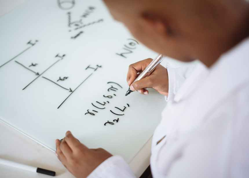 A man writes out math formulas on a horizontal whiteboard. Dyslexia anxiety in the workplace may be caused by the inability to show one's work despite arriving at the right answer.