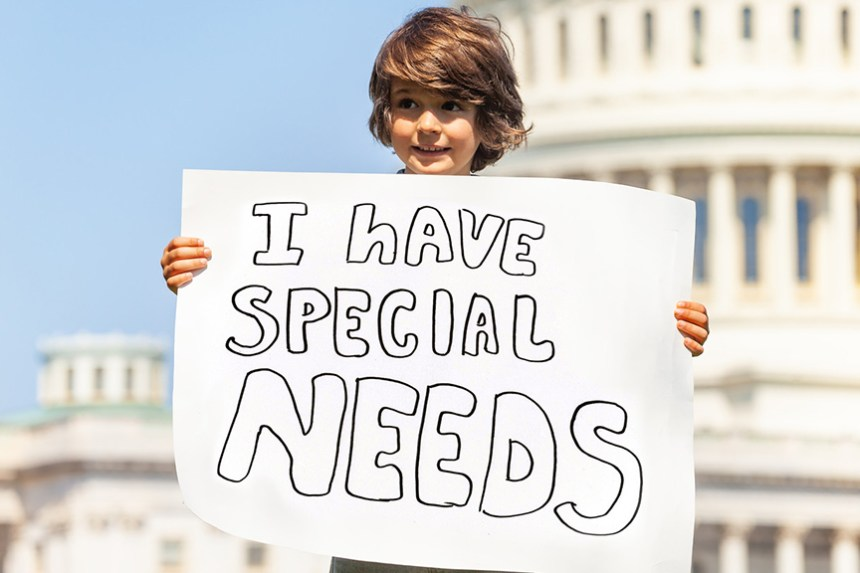 """A ten-year-old child stands in front of a building that looks like a government building holding a hand-lettered sign that says, """"I have special needs."""" Dyslexia: The Needed Revolution is a video interview with Stephen Straus of Impact Dyslexia, which works to improve the lives of students with dyslexia."""