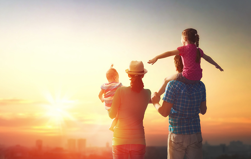 A young mother and father holding a five-year-old girl and a baby girl stand on a hillside with their backs to the camera as they gaze at the sun setting behind a city skyline in the distance. Part of practicing self-care for families involves spending time away from screens and if possible, outdoors.