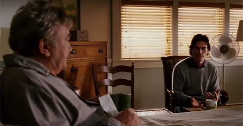 A scene from the movie Big Fish where father and son sit at at table in what might be tense conversation. This movie reveals the value of family history because it's not always easy to obtain those histories.