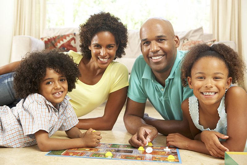 A family smiles at the camera as they play board games on the living room floor. Although times may be challenging, these back to school quotes from Thomas Mitchell remind us that there are always ways to find happiness.
