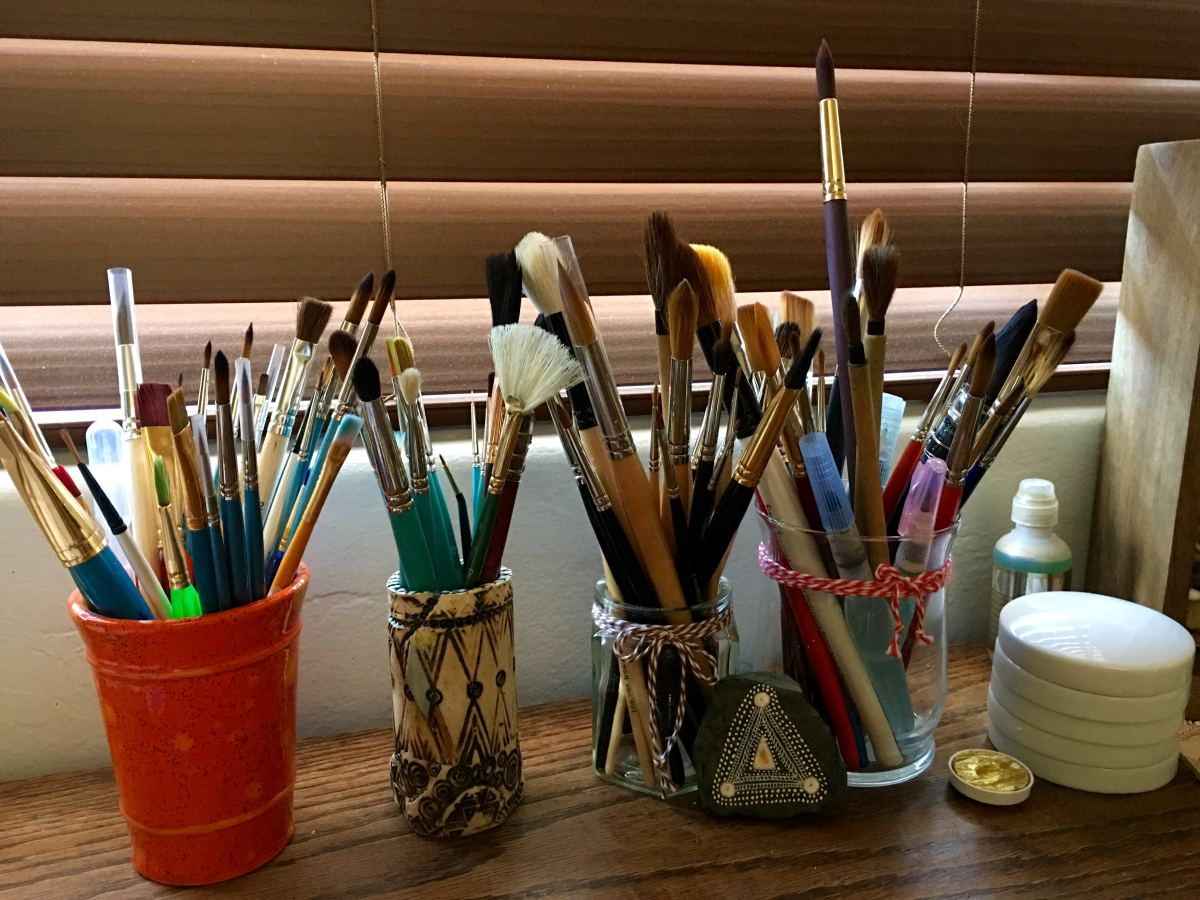 lots of watercolor brushes on container and jars on a desk