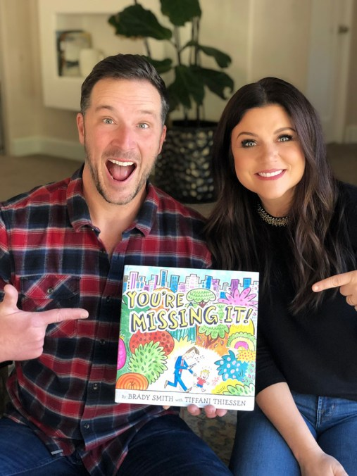 Photo of Brady Smith and Tiffani Thiessen holding new book You're Missing It!