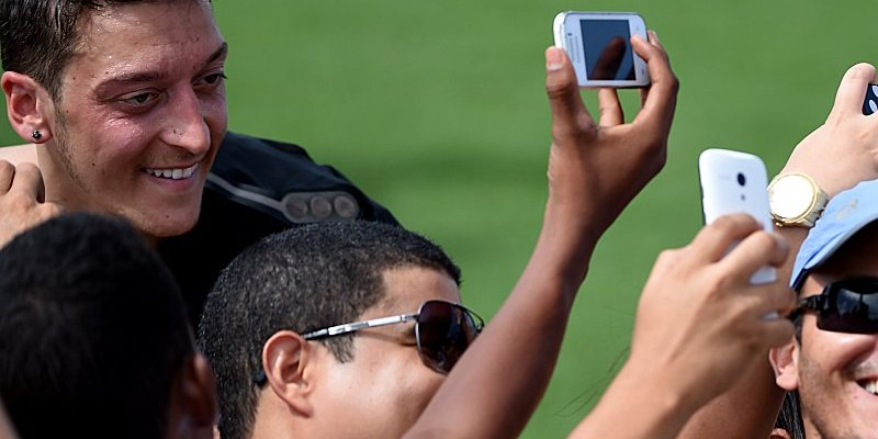 Germany's midfielder Mesut Ozil (L) poses with fans taking pictures after a training session of Germany's national football team in Santo Andre on June 9, 2014 ahead of the 2014 FIFA World Cup football tournament. AFP PHOTO / PATRIK STOLLARZ        (Photo credit should read PATRIK STOLLARZ/AFP/Getty Images)