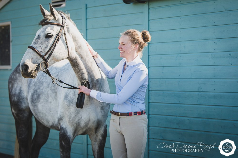 A portrait of a girl and her grey horse by a blue shed