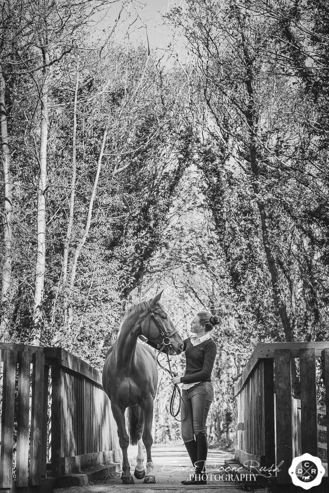 A black and white image of a girl and her horse on a bridge on the wirral way