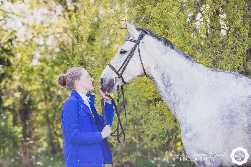 Girl kissing her grey horse