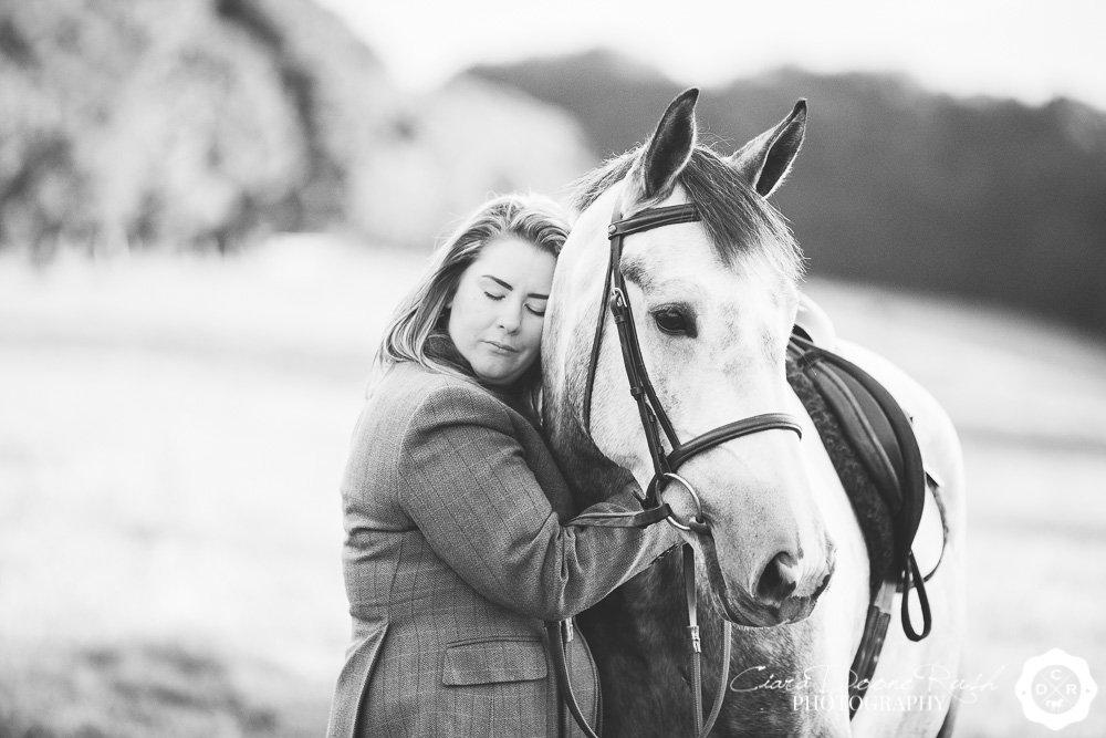a woman cuddling her horse